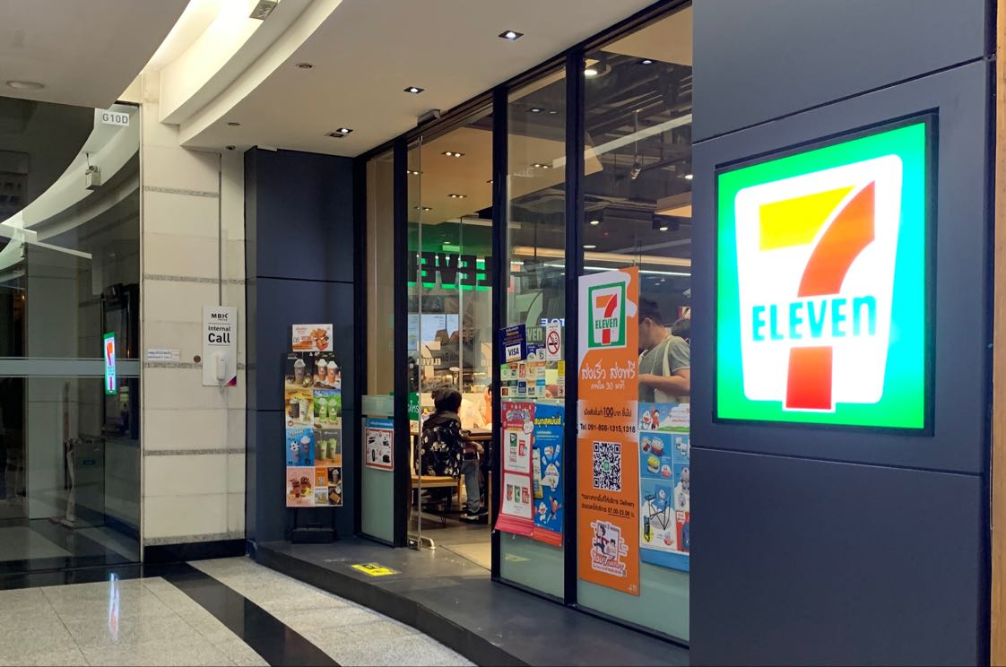 Jika kamu sedang berkunjung ke Bangkok, kamu akan banyak menemukan gerai 7 Eleven yang buka 24 jam. Salah satunya terletak di sisi kiri Hotel Pathumwan Pricess yang satu bangunan dengan MBK Shopping Center yang sangat terkenal itu.